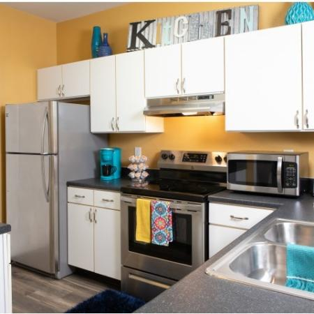 Kitchen with white cabinets and stainless steel appliances | The Lodge on the Trail Apartments near Purdue