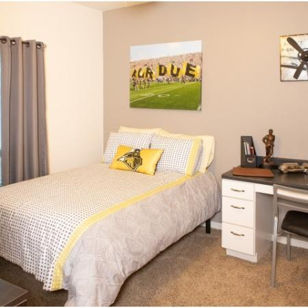 Furnished bedroom including desk and TV | The Lodge on the Trail Apartments