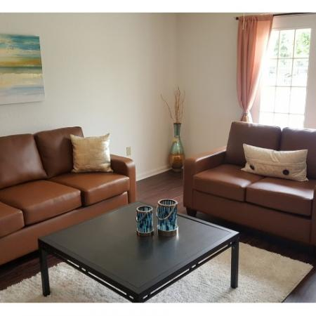 Spacious living area with wood-look floors | Hilltop Club Apartments in Bowling Green