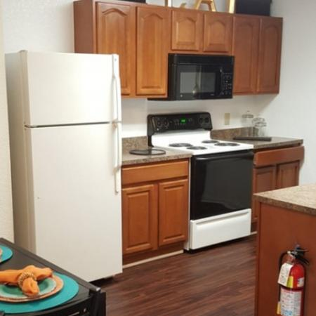 Kitchen with wood cabinets and granite counters with dining space | Hilltop Club Apartments