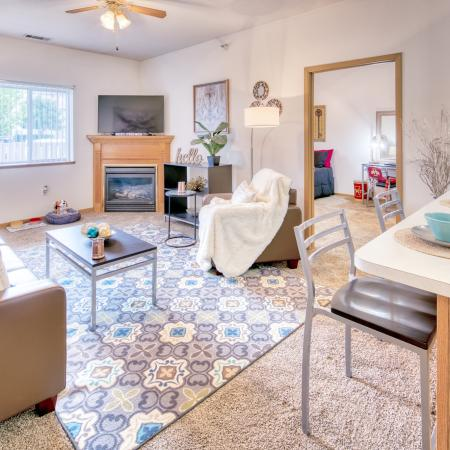 Spacious living area with ceiling fan and fireplace | South Duff Apartments