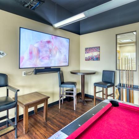 Game room with foosball, billiards, air hockey, TV, and seating | South Duff Apartments near ISU