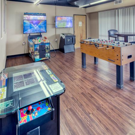 Game room with foosball, billiards, air hockey, arcades, TV, and seating | South Duff Apartments near ISU