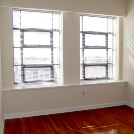 Living room with bright windows at Sydnor Flats Apartments