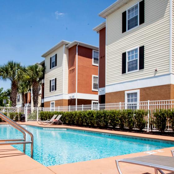 College Station, exterior, sparkling blue swimming pool, three level building, palm trees, lounge chairs