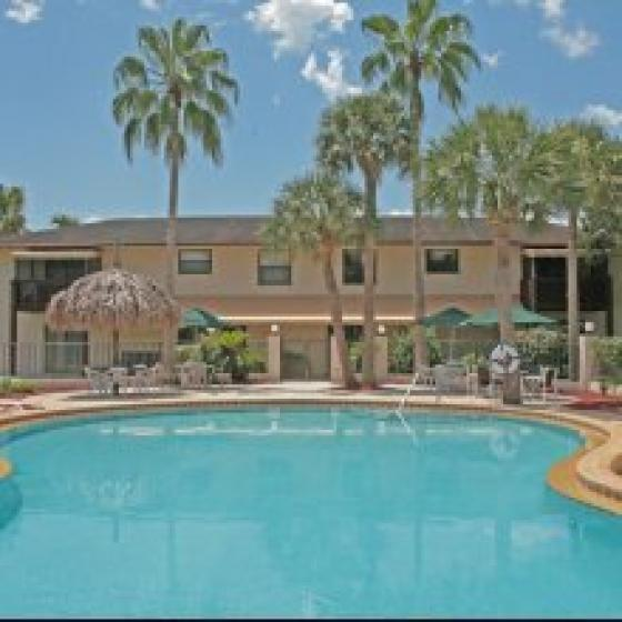 Marcell Gardens Apartments, exterior, sparkling blue swimming pool, two story building, palm trees