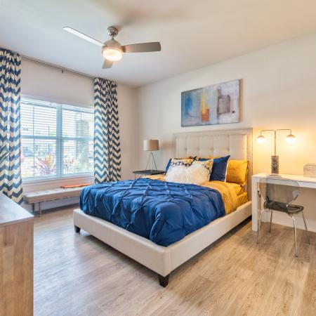 The Reserve at Coral Springs, interior, spacious bedroom, wood floors, bed, dresser, large window, ceiling fan