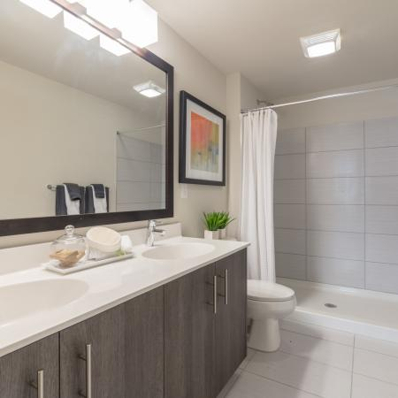 The Reserve at Coral Springs, interior, bathroom, shower, double sink vanity, dark cabinets, toilet, large mirror