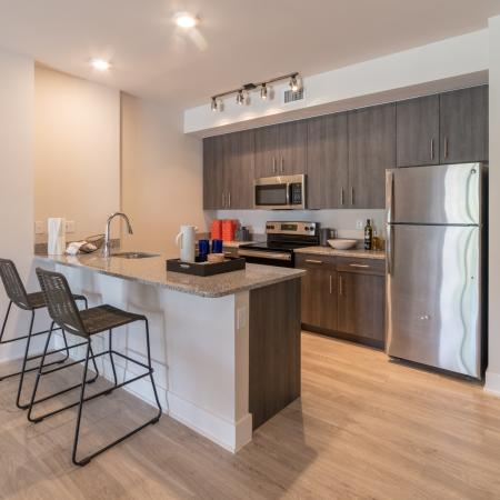 The Reserve at Coral Springs, interior, kitchen, wood floor, stainless steel refrigerator, microwave, stove/oven, dark cabinets, breakfast bar counter