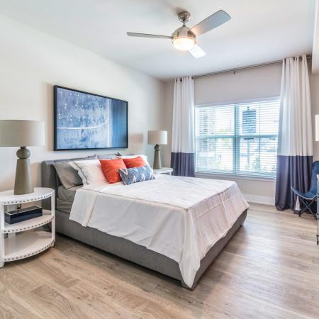 The Reserve at Coral Springs, interior, spacious bedroom, wood floors, bed, dresser, ceiling fan, large window