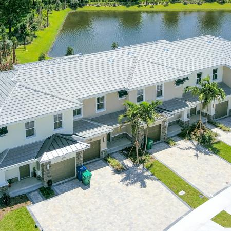 The Reserve at Coral Springs, exterior, aerial view of townhouses with garages, landscaped, pond