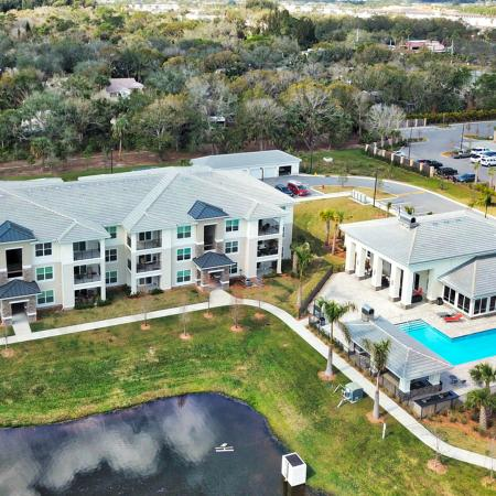 The Reserve at Vero Beach, exterior, aerial view of pond, clubhouse, pool, apartment buildings