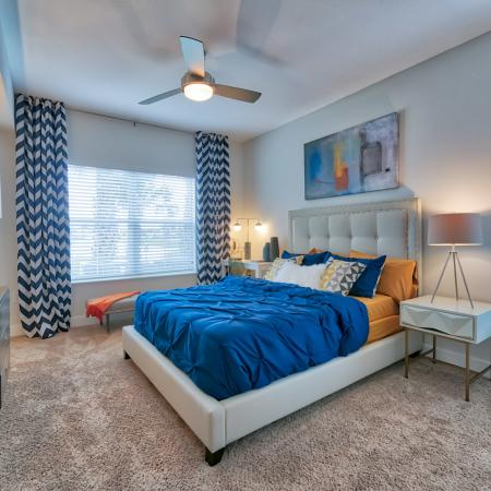 The Reserve at Vero Beach, interior, spacious bedroom, ceiling fan, carpet, bed, dresser, 2 large windows