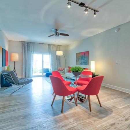 The Reserve at Vero Beach, interior, open concept, dining room, living room, ceiling fan, large sliding glass doors, wood floors, doorway to carpeted bedroom