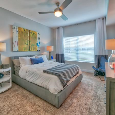 The Reserve at Vero Beach, interior, spacious bedroom, ceiling fan, carpet, bed, dresser, large window