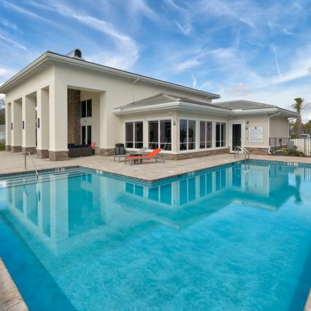 The Reserve at Vero Beach, exterior, sparkling blue pool, clubhouse, lounge chairs, palm trees