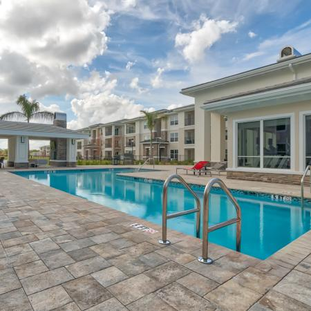 The Reserve at Vero Beach, exterior, sparkling blue pool, clubhouse, pavilion, lounge chairs, palm trees