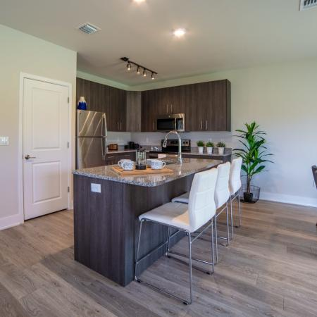 The Reserve at Coral Springs, kitchen, wood floors, spacious island with sink, dark cabnets, stainless steel appliances, refrigerator, microwave, stove/oven