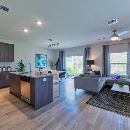The Reserve at Coral Springs, interior, kitchen, living room, open concept, wood floor, dark cabinets, microwave, stove/oven, ceiling fan, dishwasher, sliding glass doors