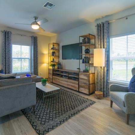The Reserve at Coral Springs, interior, living room, large windows, natural light, stylishly furnished in grays and blues