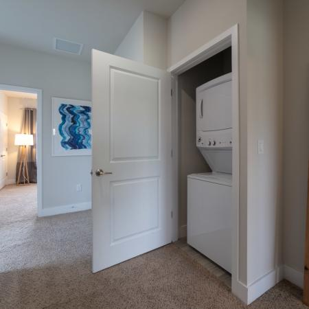 The Reserve at Coral Springs, interior, hallway closet laundry, stack-able white washer and dryer, carpeted floors