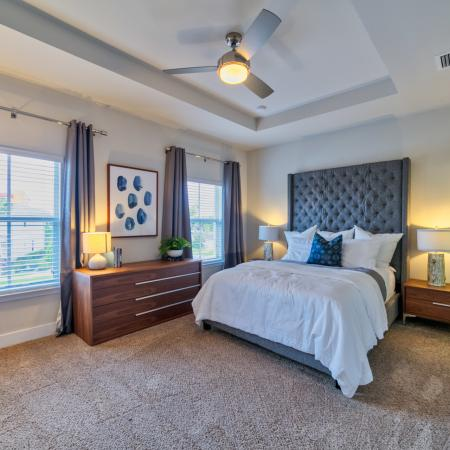 The Reserve at Coral Springs, interior, spacious carpeted bedroom, large windows, ceiling fan, bed, dresser, nightstand