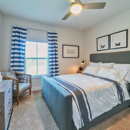 The Reserve at Coral Springs, interior, bedroom, bed, dresser, night stand, large window, carpeted, ceiling fan