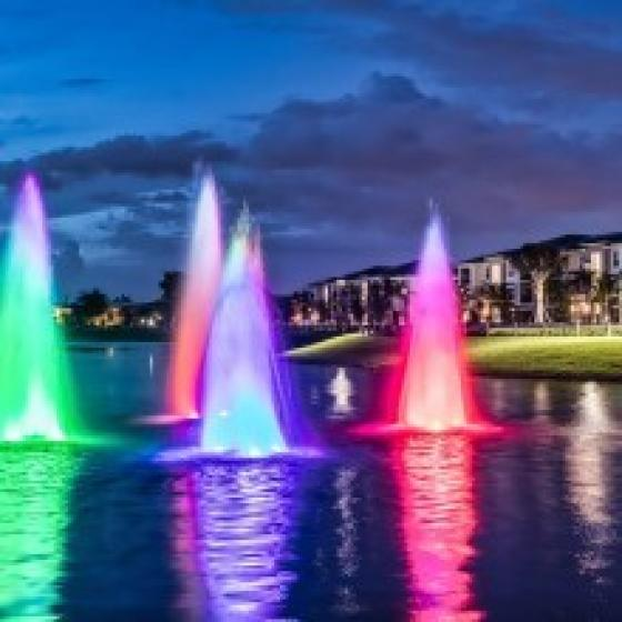 The Reserve at Coral Springs, exterior, night, rainbow fountains in pond, buildings