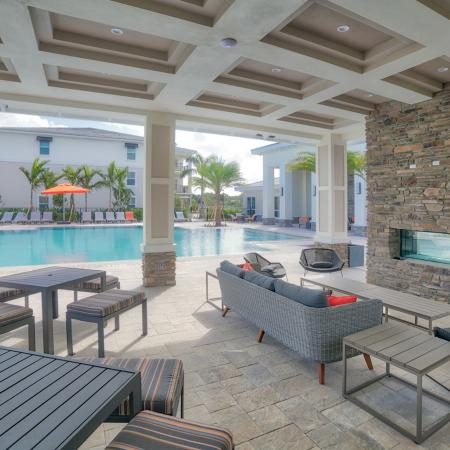 The Reserve at Coral Springs, exterior, sparkling blue swimming pool, clubhouse, lounge chairs, outdoor seating, fireplace