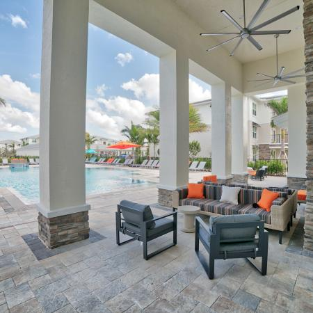 The Reserve at Coral Springs, exterior, sparkling blue swimming pool, clubhouse, lounge chairs, outdoor shaded seating