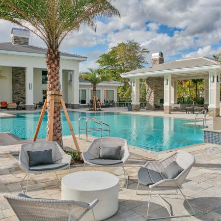 The Reserve at Coral Springs, exterior, sparkling blue swimming pool, clubhouse, lounge chairs, outdoor seating