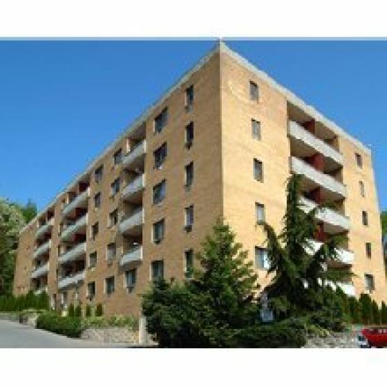 Glen Arms Apartments, exterior, light tan brick building, 5 levels, trees