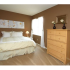 Glen Arms Apartments, interior, bedroom, cream carpet, white bed, light dresser, flower wall art. large window