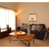Glen Arms Apartments, interior, living room, large windows, carpet, dark sofat, coffee table, lamps, pillows, wall art