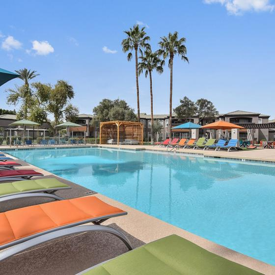 Pool area with lounge chairs and umbrellas