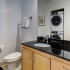 Bathroom with one sink, toilet, shower, and stacked washer/dryer