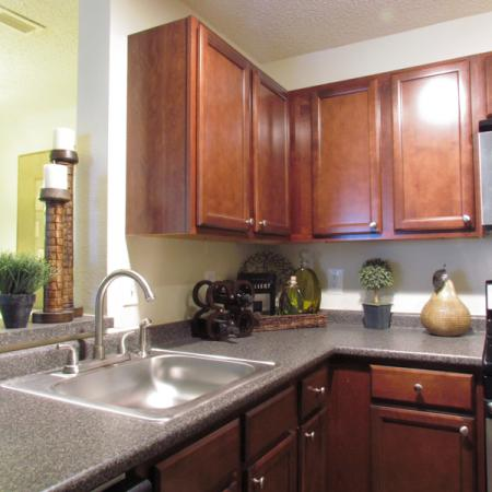 Renovated kitchen with dark wood cabinets and gray countertops | 2 bedroom apartment at The Pavilions
