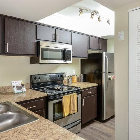 Kitchen with hardwood floors, stainless steel appliances, built in microwave, espresso cabinets   Village Place apartment homes