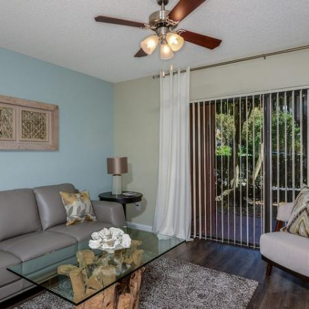 Living room with hardwood floors and ceiling fan | Village Place West Palm Beach