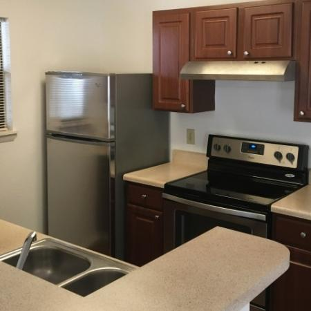 Renovated kitchen with dark wood cabinets and stainless steel appliances