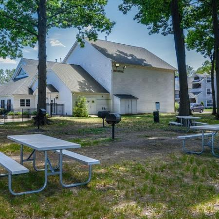 Community picnic tables and charcoal grills | outside at The Pavilions apartment community