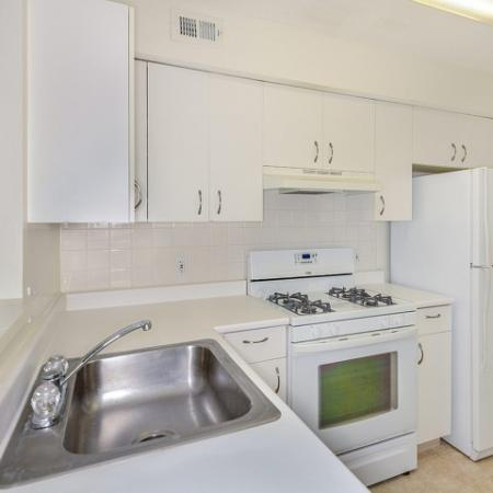 Apartment kitchen with white cabinets and white appliances including gas range | Residences at Westborough apartments