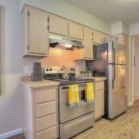 Kitchen with light wood cabinets, wood floor, and stainless steel appliances | Vizcaya 1 bedroom apartment