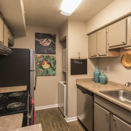 Kitchen with stainless steel appliances and stacked washer and dryer | Vizcaya apartments