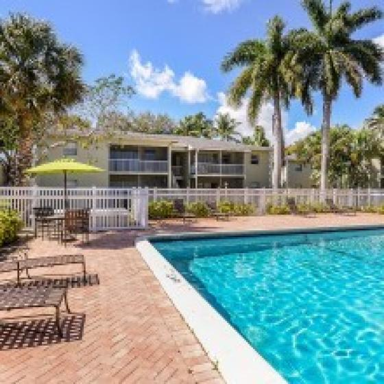 Greentree, exterior, sparkling blue swimming pool, lounge chairs, balconies, palm trees