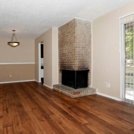 Apartment living room with fireplace with brick surround | Royal Crest in Tyler TX
