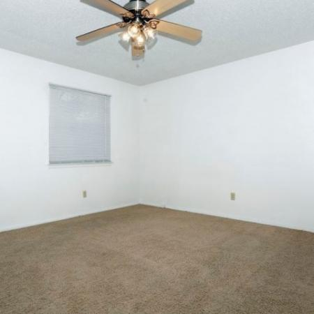 Bedroom with carpeting and ceiling fan | Royal Crest apartment