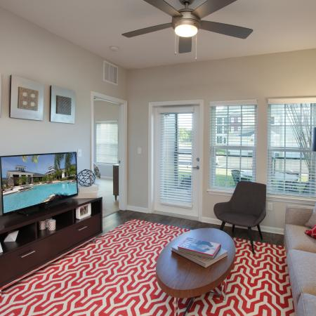 Apartment living room with hardwood floors, ceiling fans and door to private patio | Village at Terra Bella rentals