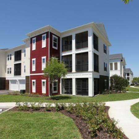 Exterior of 3 story apartment buildings with attached garages and screened-in porches | Village at Terra Bella in Land O' Lakes FL