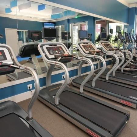 Treadmills with tvs at apartment gym | Village at Terra Bella